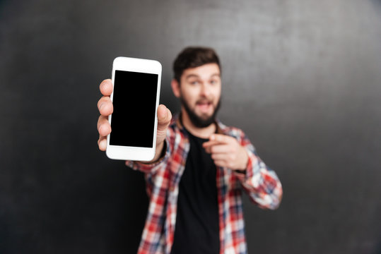 Smiling man holding and showing blank screen cell phone