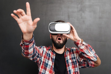 Surprised man wearing virtual reality device standing over chalkboard