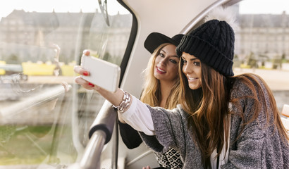 France, Paris, two smiling women taking a selfie on a tour bus