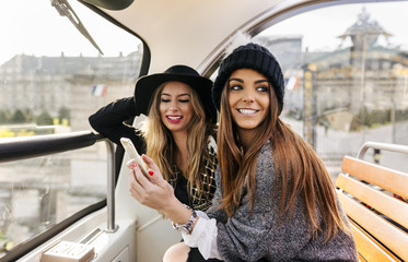 France, Paris, two smiling women with cell phone on a tour bus