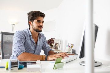 Portrait of male programmer using computer in a bright office.