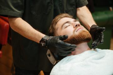 Bearded man getting beard shaving by hairdresser