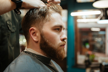 Young man getting haircut by hairdresser with scissors