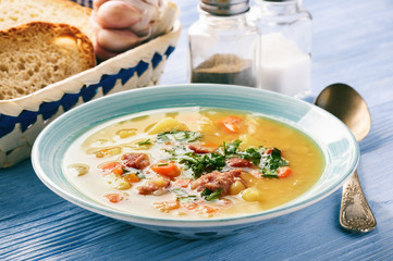 Pea soup with smoked sausage on blue wooden background.