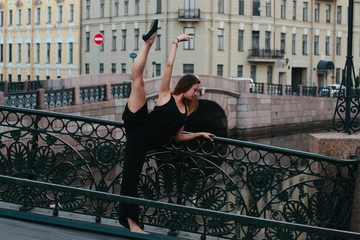 young and graceful woman performing gymnastic exercises outdoors