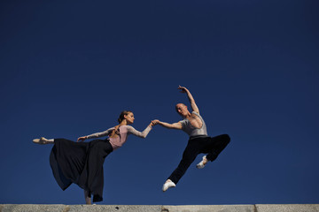 young woman and a man performing gymnastic exercises against the