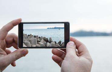 man photographs a mobile phone