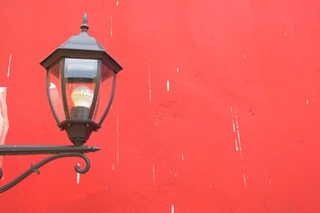 Beautiful vintage lamp on the red wall