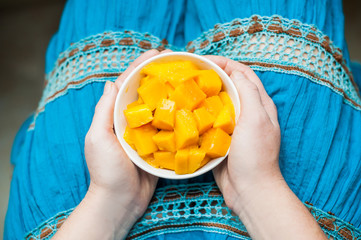 Bowl of healthy fresh mango in the hands of a young woman