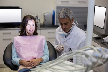 Dentist showing mouth model to female patient