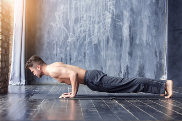 Yoga men workout on black mat.