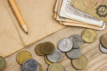 Old notes and coins and pencil on a wooden table