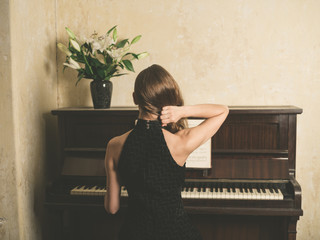 Young woman in dress by piano