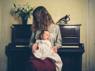 Young woman with baby by piano