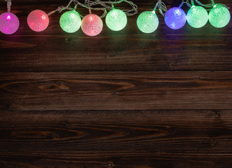 Christmas light ornaments on old wood background.