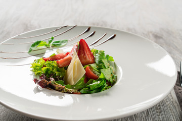 Salad greens, cheese and strawberries with balsamic sauce.