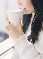 Woman drinking hot drink, mid section