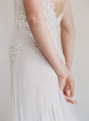 Bride wearing wedding dress, hands behind back, mid section