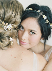 Two women wearing bridal wear, hugging