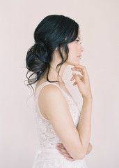 Portrait of bride in bridal wear, resting head on hand, side view