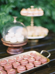 Macarons on tray on wooden table with deserts