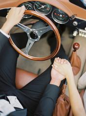 Couple sitting in vintage car, holding hands, mid section