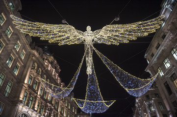 Christmas lights twinkle in the night sky above Regent Street, in London