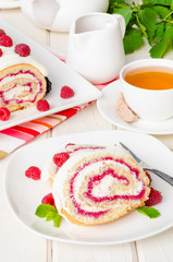 Vanilla roulade with raspberry jam and butter cream on a white background
