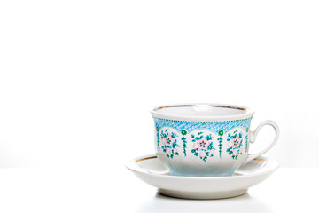Ornamental tea cup with saucer on white background. Porcelain dishes, kitchenware. Decorative background.