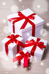winter holiday concept - present boxes with red ribbon on wooden