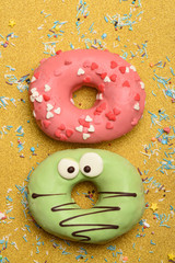 Funny glazed donuts on gold background