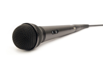 Black vocal microphone with on button on body and wire isolated on white background side view closeup