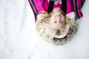 Young girl lying in snow, overhead view