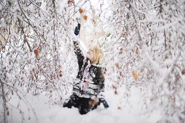 Girl sitting in snow, under snow covered tree, reaching up to branches