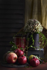 Pomegranates and apples on table, jug of flowers behind