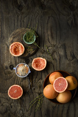 Whole and sliced grapefruits, with fruit squeezer and fresh thyme