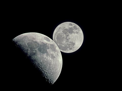 Close-up of  full Moon behind the waxing gibbous moon (50% of full) on dark sky with copy space - Double Moon in the dark