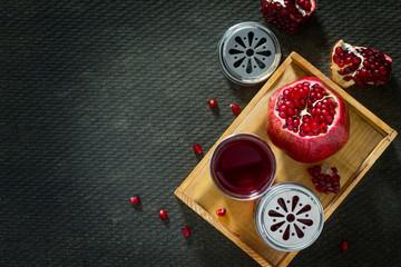 Pomegranate and pomegranate juice on a concrete gray background.