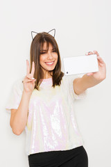 Modern millennial young woman taking a selfie on smart phone