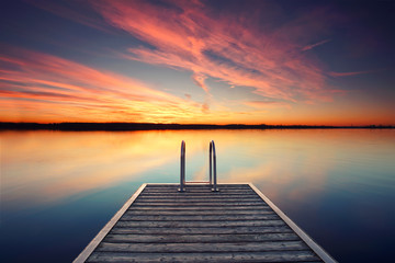 einsamer Holzsteg am See mit Treppe zum Wasser