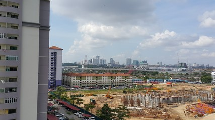 High angle view of cityscape with construction site and high rise over cityscape on sunny day in Johor Bahru, Malaysia