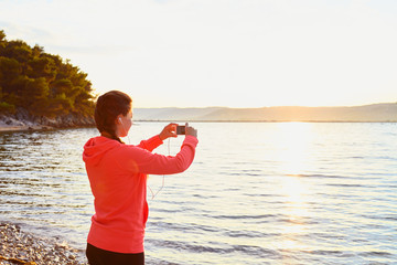 Young woman makes photo at beach after run
