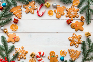 Christmas cookies with candy and  festive branches fir. Homemade delicious Christmas gingerbread cookies on the wooden background. Free space for your text.