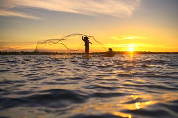 Silhouette of traditional fisherman throwing net fishing lake at sunrise time