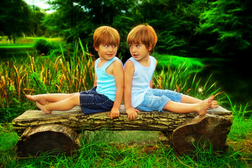 Adorable Little Twin Brothers Sitting On A Wooden Bench Smiling And Looking At Each Other Near The Magical Lake At Summer, Vivid Colors