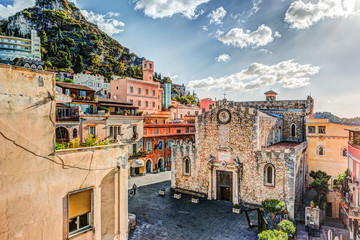 The Duomo in most popular sicilian resort Taormina. Aerial view. Townscape of Taormina with cathedral, square and the hill with other buildings. Wall mural