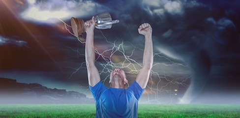 Composite image of happy rugby player holding trophy 3D