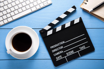 Movie clapper with a cup of coffee and keyboard on blue wooden table