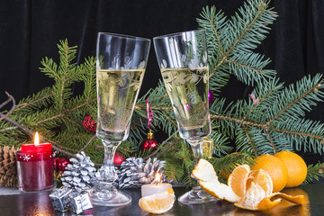Christmas composition with two glasses of champagne, mandarins and burning candle on black background