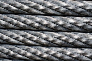 Steel sturdy, heavy duty cable wires.  Up close of cable wire that is wrapped around coil.  Industrial strength wire for tie down or zip line.